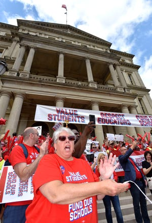 Paula Herbart, President of the Michigan Education Association, cheers on the steps of the Capitol during the 'Red For Ed,' rally in Lansing Tuesday.