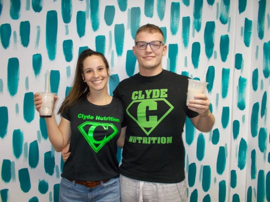 The proprietors of Clyde Nutrition, Halle McGinn and Marshall Messer, hold one of their nutrition shakes.