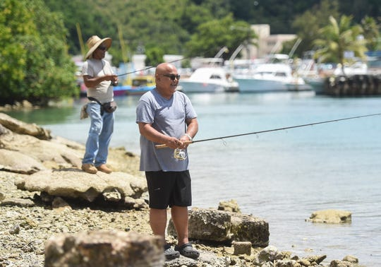 Barrigada resident John Cruz, 60, front, sets out for an afternoon of fishing in Agana Bay on June 18, 2019. While positioning himself along the shore, Cruz stated that the two reasons he fishes are for sport and food.