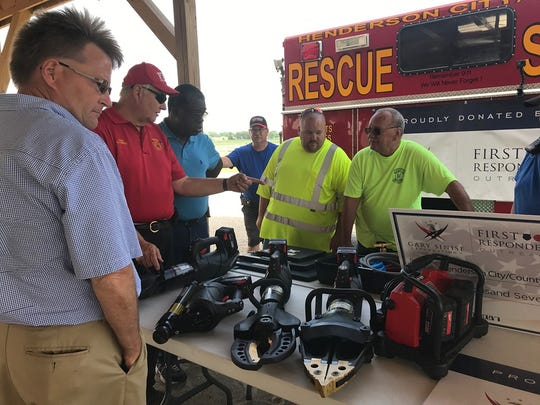 """Henderson City Manager William """"Buzzy Newman (left, front), Niagara Fire Chief Glenn Powell, Kenny Perkins, Justin Durbin and Smith Mills Chief Mike Coghill look at the new extrication equipment the Henderson City County Rescue Squad purchased thanks to a grant from the Gary Sinise Foundation (June 17, 2019)."""