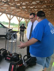 Rescue Squad Assistant Chief Bryan Coghill talks to Judge-executive Brad Schneider about new equipment purchased with a grant from the Gary Sinise Foundation.