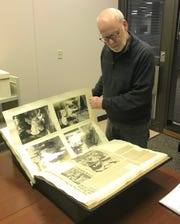 George Rugg, curator of special collections at Notre Dame's Hesburgh Library, leafs through a Gene Tunney scrapbook kept by former trainer Bill McCabe