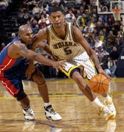Pacers Jalen Rose (#5) drives around Detroit's Jerry Stackhouse in 2002.