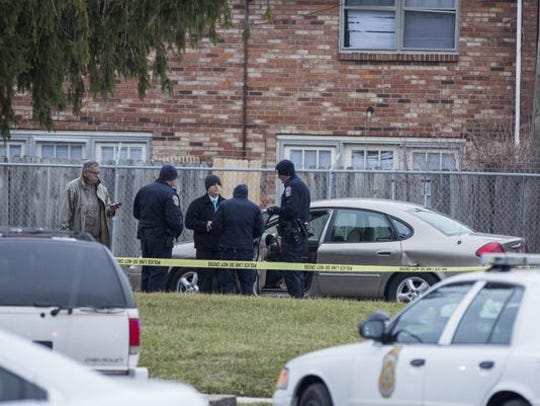 Homicide detectives and IMPD officers gather around a tan Ford Taurus in the 4400 block of Park Forest Court on Feb. 3, 2016.
