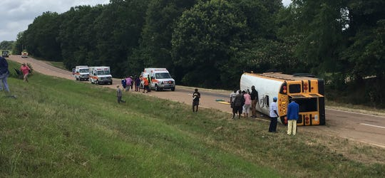 This photograph provided by Ken Strachan, director of the Carroll County Emergency Management/Civil Defense Agency, shows a Greenwood School District school bus on its side on U.S. 82 near McCarley Road in Carroll County, Mississippi, Monday, June 17, 2019. Several Greenwood High School students were injured in the one-vehicle accident and were taken to area hospitals.