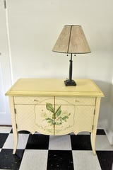 The pale yellow paint on this cabinet pops against the black and white checkered floor in the kitchen area at Hopecote.