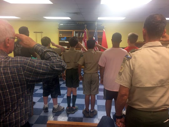 Members of Troop 157 open their meeting with the Pledge of Allegiance.