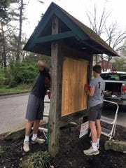 James Walker Whitehead, left, and Carson Whitehead finish their Boy Scout project of refurbishing the kiosks leading into the Broadacres subdivision.