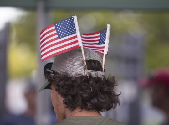A man wears American flags in his hat during the Uncle Sam Jam to celebrate Independance Day at Parc International in Lafayette Monday, July 3, 2017.