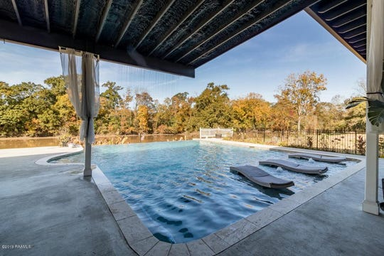 An infinity edge pool and shaded seating area face the Vermilion River on a half-acre plot of land.