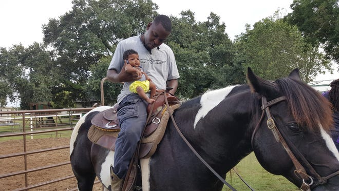 Arie Lewis has been riding horses since she was four weeks old, as pictured above, with her dad Christopher Lewis.