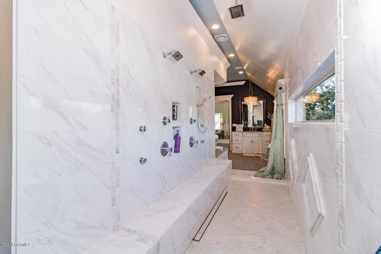 The spa-like master bathroom has a 14-foot walk-through shower that overlooks the Vermilion River.