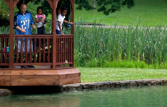 La'Mariya Martin, 8, center, pulls a fish out of a pond at Rising Park as she fishes with her father Larry Martin, left, and brother Tre'Sean Tyler, 6, Tuesday, June 18, 2019, in Lancaster. The trio were fishing from the gazebo next to the pond to avoid the rain.