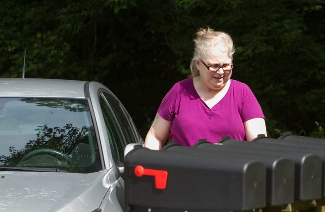 Lynne Gatz, 60, from Howell, pulls up to retrieve her mail Tuesday, June 18, 2019 on Grand River Avenue after traveling from her home on Maple Crest Drive. The trip to Gatz's mailbox is not directly on the way home, nor is it a walk she's able to do given her disability.