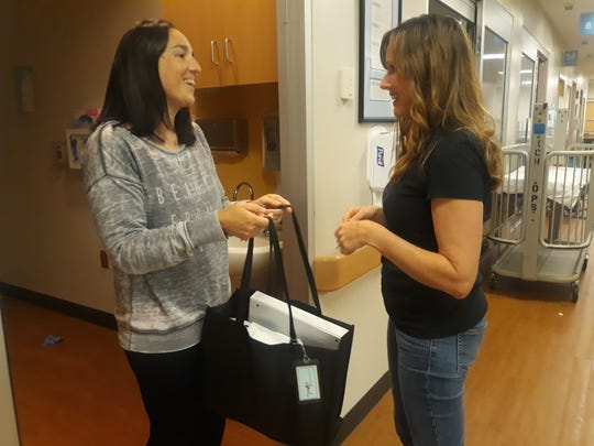 """TyiaLynn Scott, right, delivers a hospital bag to Sondra Esposito on Monday, June 17, 2019 at Norton Children's Hospital in Louisville, Ky. Esposito said she loves what Scott does to help families. """"It's sometimes difficult to keep your faith when faced with your child's pain and fight for life,"""" she said. """"Critically Loved is a safe place to be reminded of His love for all of us."""""""