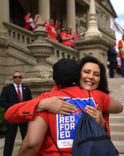 Michigan Governor Gretchen Whitmer hugs a rally goer Tuesday, June 18, 2019, during the MEA #RedforEd Rally for Public Education at the State Capitol in downtown Lansing, Michigan.  [AP Photo/Matthew Dae Smith/Lansing State Journal]