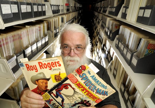 Randy Scott, comic art bibliographer at MSU, shows a Roy Rogers comic from 1953 and a Spiderman comic from  1964, part of  MSU's huge comic book collection in the Special Collections area at the MSU Library Monday August 24, 2009.