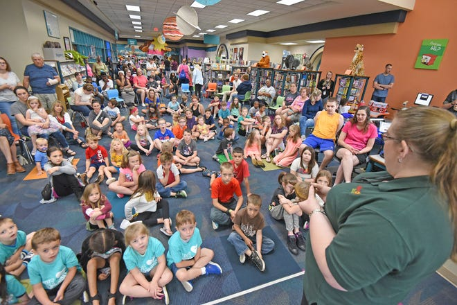 Akron Zoo Education Specialist Carrie Bassett shows children and adults a turtle named Shelly on Tuesday morning during a demonstration of zoo animals at the Mansfield/Richland County Library.