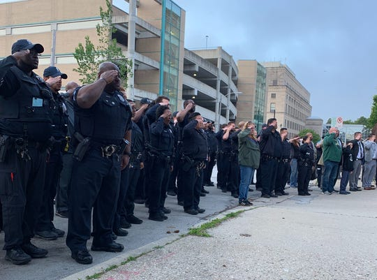 Officers salute as the body of  Milwaukee Police Officer Kou Her arrives at the Milwaukee County Medical Examiner's Office Tuesday morning. The off-duty officer was killed in an overnight car crash.