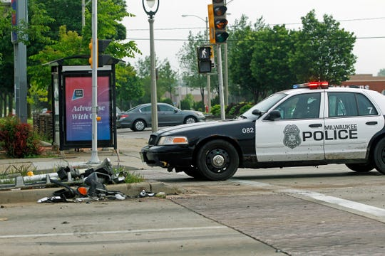 A Milwaukee Police officer is at the scene Tuesday where an off-duty Officer Kou Her was killed in a crash when a repeat drunken driver ran a red light at North 60th and West Capitol Drive.