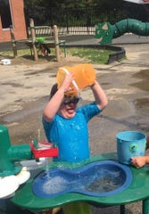 Joshua Harris plays with the water table in an outside area at Every Child's Place in Kenosha.