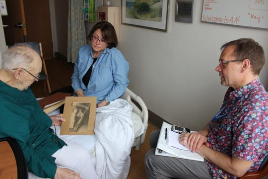 Thor Ringler (right) interviews Ray Miller (left) in his room at the William S. Middleton Memorial Veterans Hospital in Madison, on April 4. Miller's daughter Barbara (center) brought old photos to help facilitate the conversation, including an old press clipping from Miller's time in the National Guard.