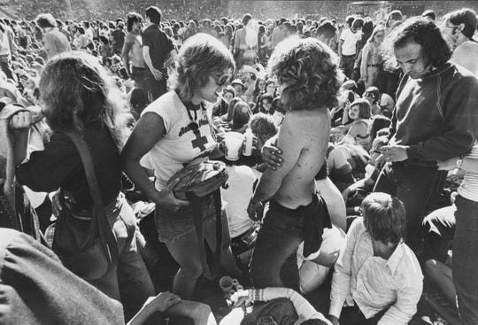 A registered nurse, one of several volunteer medics on hand, pours water for a dehydrated fan during the Rolling Stones concert at County Stadium on June 8, 1975. This photo was in the June 9, 1975, Milwaukee Journal.