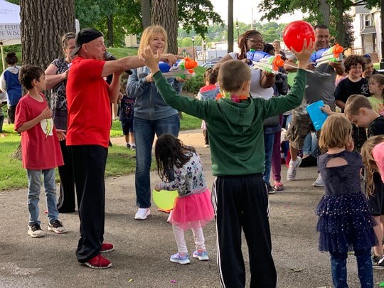 """Gene Covelli, an entertainer with GNO Productions, instigates a water fight among participants as part of the Kids Are People Too program. The June 17 activities preceded the showing of """"Spider-Man: Into the Spider-Verse,"""" the first film to be shown this summer in the city of Waukesha's Monday Night Movies in the Park series."""