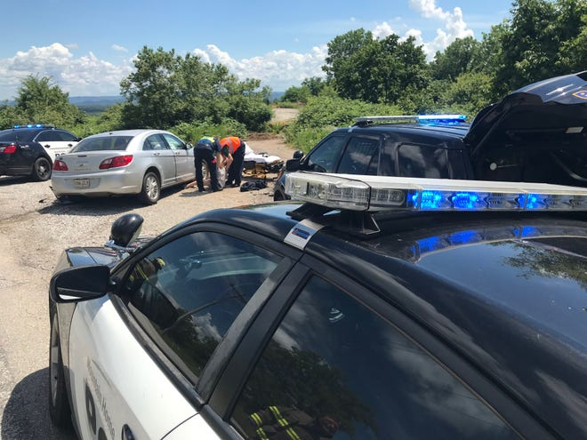 Medical personnel tend to one of two female juveniles Mountain Home police say started a pursuit Tuesday afternoon when an officer spotted a Chrysler Sebring they were driving that had been reported stolen. The pursuit ended on Baxter County Road 69 when they crashed the car into a Chevrolet truck, causing the truck to roll on its' side.