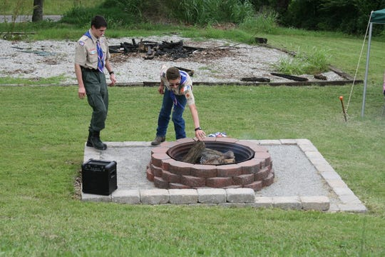 "Eagle Scouts Logan Coleman and Cody Marquis add wood to the fire inside a ""flag retirement ring"" on Saturday afternoon. Marquis constructed the ring outside the Cotter Fire Department as part of his Eagle Scout Project as a way to properly dispose of torn and tattered American flags."