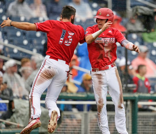 Louisville's Drew Campbell, right, celebrates with Alex Binelas (13) after scoring against Auburn on a fielding error in the fourth inning of an NCAA College World Series baseball game in Omaha, Neb., Tuesday, June 18, 2019. (AP Photo/Nati Harnik)