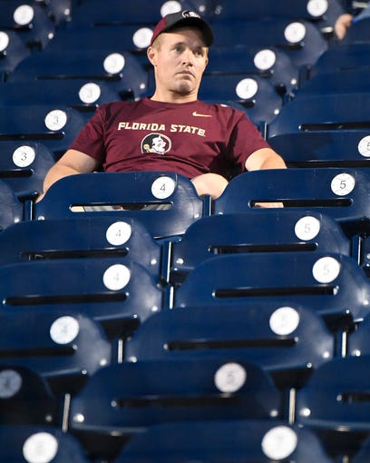 A Florida State fan sits in the stands after a 2-0 loss against Michigan in their 2019 NCAA Men's College World Series game at TD Ameritrade Park Monday, June 17, 2019, in Omaha, Neb.