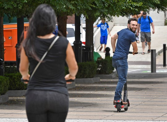 A scooter rider looks back to make sure his friend is still following June 18, 2019, in Nashville.