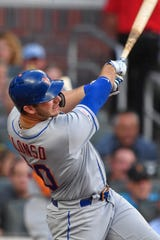 New York Mets first baseman Pete Alonso (20) singles to drive in a run against the Atlanta Braves during the third inning at SunTrust Park.