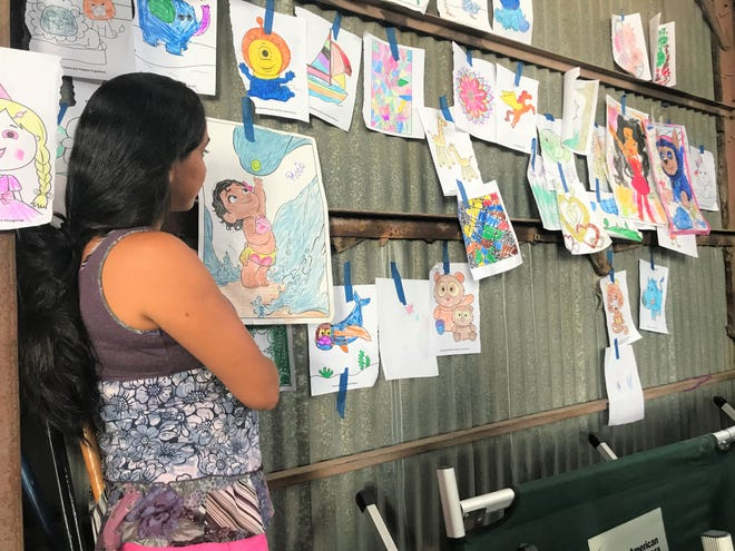 """Hayssell Marvenia Dera-Aroche, 26, looks on at her 4-year-old daughter, Rocio's colored-in picture of """"Moana"""" the movie."""