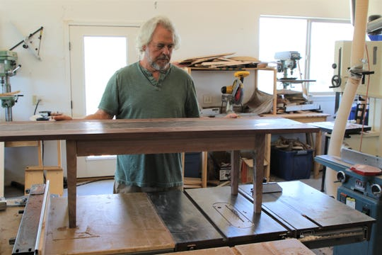 Artist Steven Barr examines a coffee table he is crafting for a client in his studio north of Aztec on June 18.