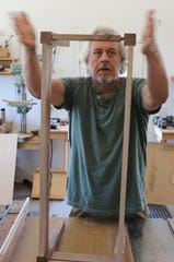 Steven Barr assembles the legs of a coffee table in his studio north of Aztec on June 18.