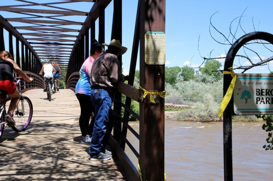 At right, Sarah and Arturo Moreno watch the Animas River, Tuesday, June 18, 2019, while bicyclists ride by on the Berg Bridge.