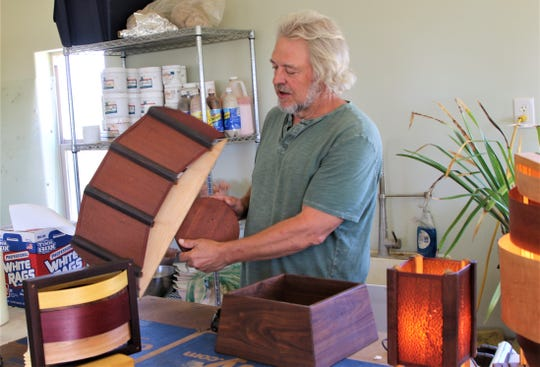 Steven Barr displays one of his wooden wall sconces in his studio north of Aztec on June 18.