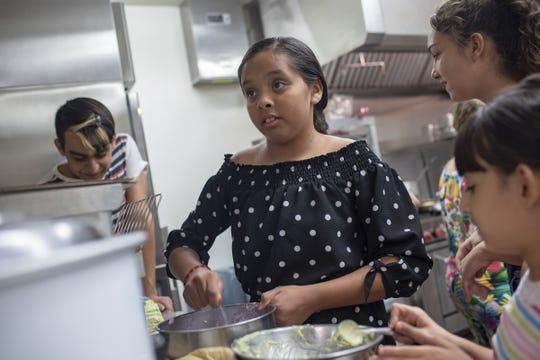 Student workers help make food during the grand opening of the school's new vegan cafe on June 7, 2019, at V.H. Lassen Elementary School in Phoenix, Ariz.