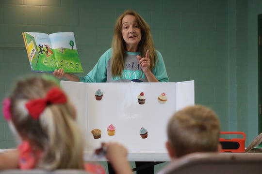 """Terri Winke, preschool coordinator at Ida Rupp Public Library, reads a story from """"Pete the Cat,"""" a popular children's book series, during Nature Story Time in Portage Township on Tuesday."""