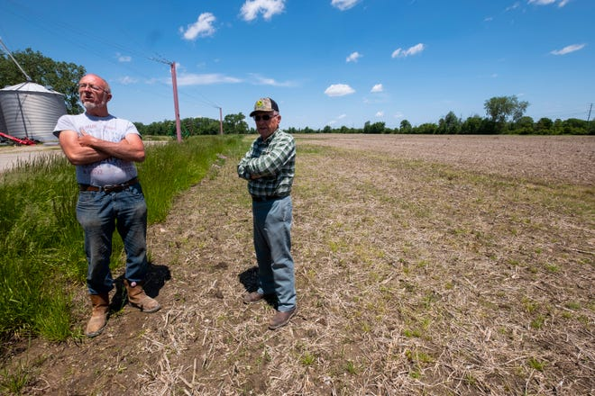 Area farmers Randy Russ, left, and Jim Domagalski stand in an empty field on Domagalski's Columbus farm Tuesday, June 11, 2019. Wet conditions have delayed area farmers from planting crops like corn and soybeans.