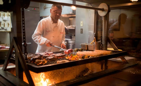 At the Hitching Post restaurant, Luis Meza works the Santa Maria-style grill fueled by local red oak coals, with a grate that can be raised and lowered.