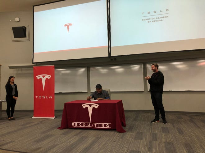 A student signs a letter of intent to take part in Tesla's Manufacturing Development Program.