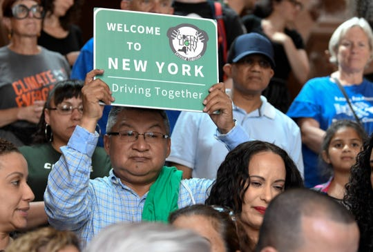 A protester holds a sign as members of the state Assembly speak in favor of legislation of the Green Light Bill granting undocumented Immigrant driver's licenses during a rally at the state Capitol Monday, June 17, 2019, in Albany, N.Y.