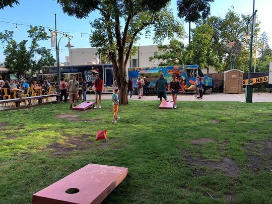 The Park, Redding's food truck hub, features games for the young and young at heart. A crowd is seen on a Friday evening in May 2019.