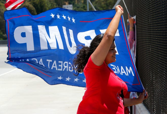 Anitra Mireles, 44, of Prunedale, waves a   Donald Trump Make America Great Again flag Tuesday on the Crazy Horse Road overcrossing on Highway 101 in Prunedale. She and others rallied to celebrate the impending announcement of his 2020 re-election campaign.