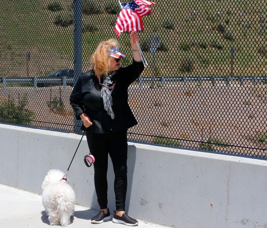 Malvina Aguilar, 60, of Salinas, waves flags at a rally on the Crazy Horse Road bridge over Highway 101 in Prunedale to celebrate President Donald Trump's expected announcement of his 2020 re-election campaign. She appeared with her bichon, Pelusa.