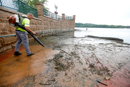 In this Wednesday, June 12, 2019 photo, Matt Cooper, with the City of Dubuque, cleans off an area of American Trust River's Edge Plaza in Dubuque, Iowa, after high water levels of the Mississippi River left large amounts of debris and mud. (Dave Kettering/Telegraph Herald via AP)