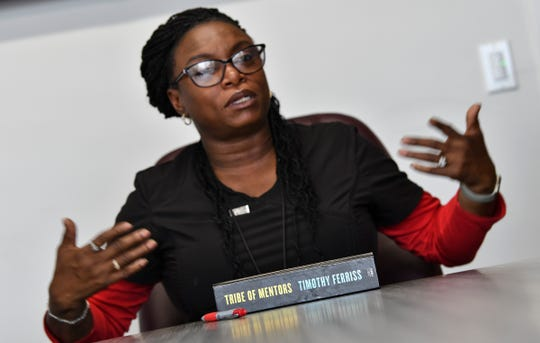 Keshia Anderson King speaks near a book on leadership given to graduates of the Jugaad Leadership Program during an interview Friday, June 14, in St. Cloud.